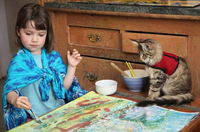 IrisGrace u trenutku inspiracije sa svojom mačkom Thulom. Nevjerojatno je da mačka Thula ostaje sjediti satima uz svoju štićenicu, sve dok Iris ne završi slikanje.